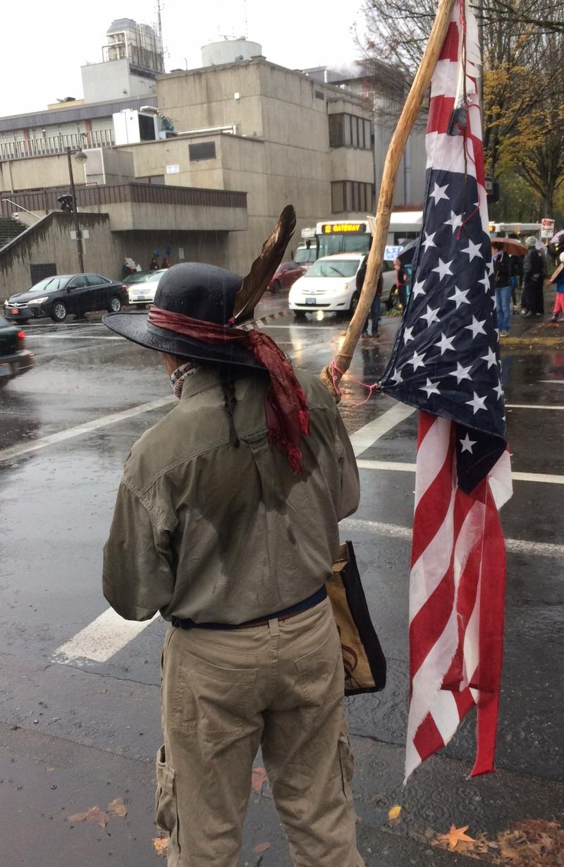 One supporter displays an upside-down American flag, indicating distress.