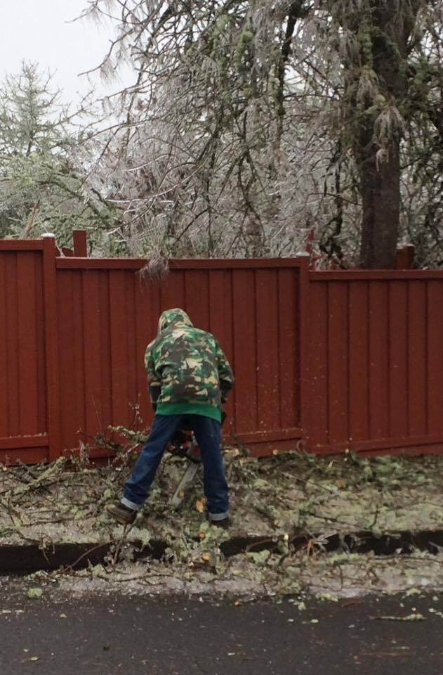 A local man uses a chainsaw on fallen branches.