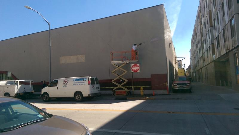 Crews are power-washing Shawmed's wall in preparation for mural.
