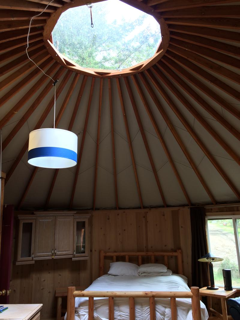 Interior of yurt, which has queen size bed, pellet stove, and flat-screen TV