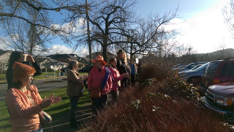 Eugene community members cheer from the sidewalk.