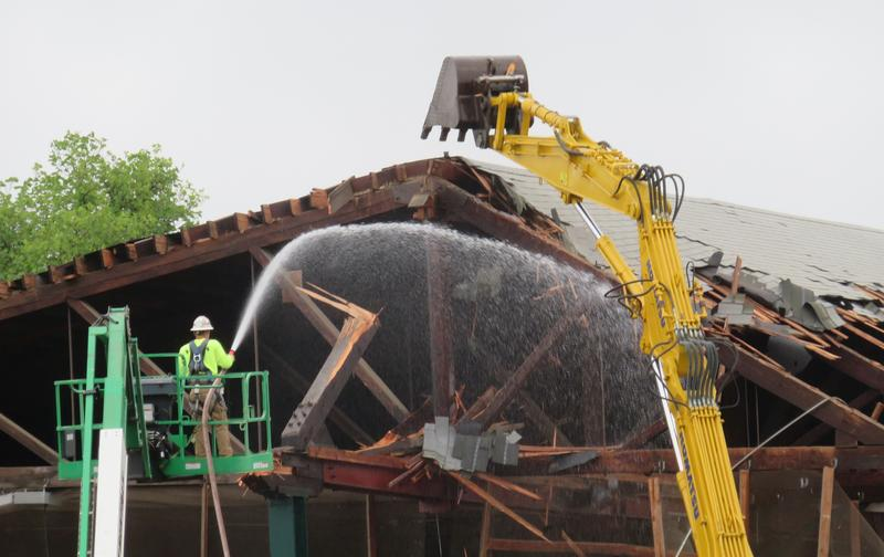 A worker hoses the structure to control dust.