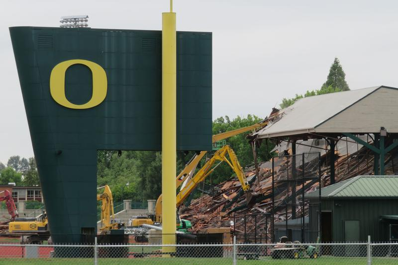 Excavators batter and tear at the East Grandstand.