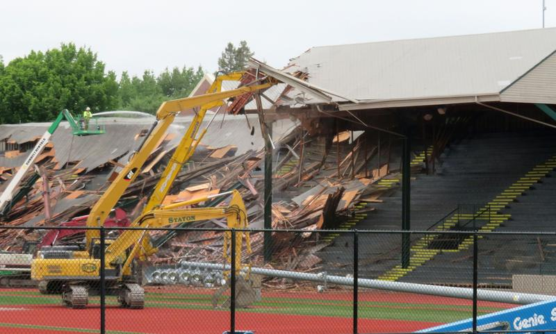 A row of excavators collapse the East Grandstand's roof.