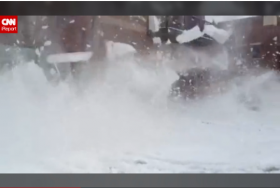 Giant chunks of snow fall from office building in Old Town Square Friday afternoon.