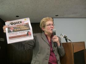Historian Aleen Ratzlaff holds up The Community Voice while speaking at the Wichita Public Library.