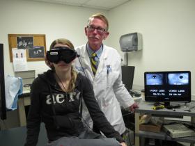 Dr. Robert Jensen demonstrates infrared goggles used to diagnose vertigo on Angelica Garcia.