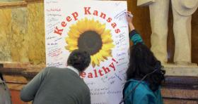 Supporters of a Medicaid expansion sign a poster before delivering it to the governor's office.