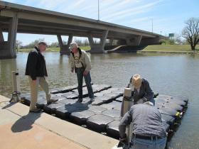 Volunteers install the new floating dock on the Arkansas River behind Gander Mountain in late April.