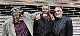 Brothers Sherman and Wendell Holmes with Poppy Dixon comprise May's featured group, the blues trio The Holmes Brothers.