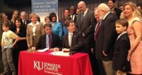Kansas Governor Sam Brownback signs HB 2744 at a ceremony at the KU Edwards Campus