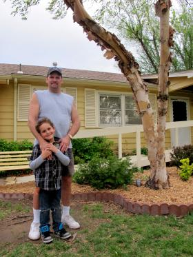 Ron Barnhart stands with his son in front of his home in West Wichita. Barnhart's private water well has been contaminated with tetetrachloroethylene