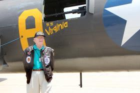 Dr. Lewis Smith, a 90-year-old WWII veteran, stands beside the plane he flew in 35 missions.