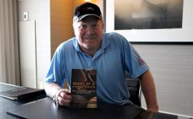 Former Denver Broncos linebacker Karl Mecklenburg poses with the book he wrote. Mecklenburg played 12 seasons in the National Football League.