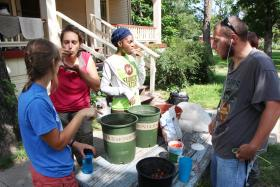 Members of Legacy GardenWorks huddle around a plastic tub of their homemade salsa.