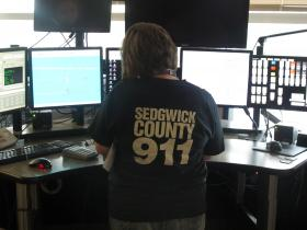 A dispatcher monitors computer screens at the Sedgwick County Emergency Communications 9-1-1 Call Center.