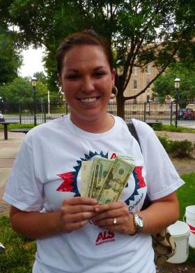 Lauren Walsh, regional development director of the local ALS association chapter, displays the $250 donated by the Kansas legislators at the challenge.