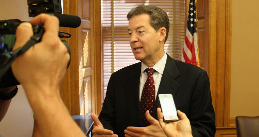 Gov. Sam Brownback speaks with reporters Monday at the Statehouse.