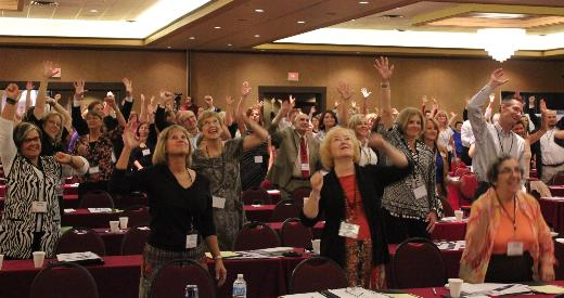 Participants in the obesity summit reach for the ceiling as part of a mid-morning activity break.