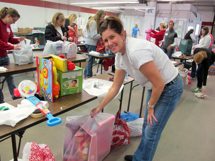 Volunteer Angela Lentino prepares gifts for a small girl.