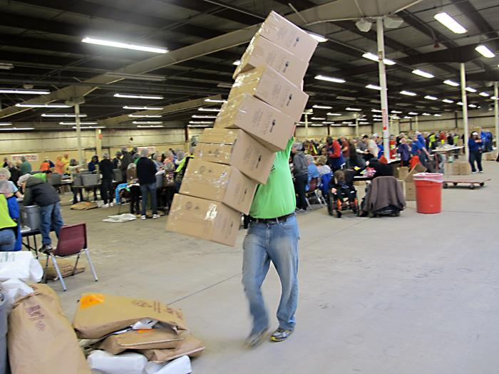 A volunteer carries a precarious stack of empty boxes to a packing table where they will be backed with food for children of Haiti.