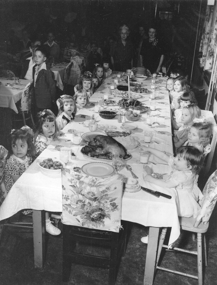 Children take part in dinnertime at the Wichita Children's Home.  Mrs. M.L. Garver founder of the Home, believed that dinner should be served to the children on white tablecloths, a practice that continued for more than 100 years.