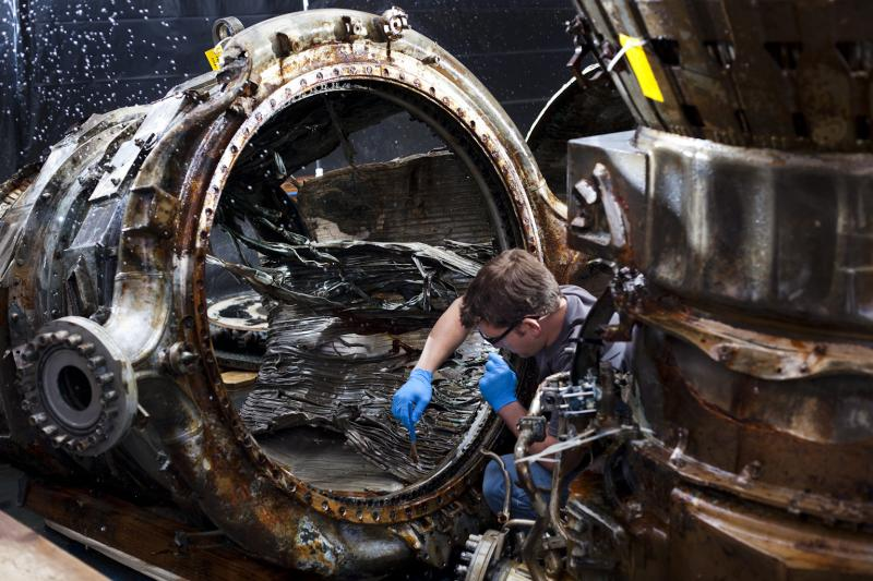 Jerrad Alexander, SpaceWorks Technician, uses a fine brush to clean an Apollo F-1 Thrust Chamber.