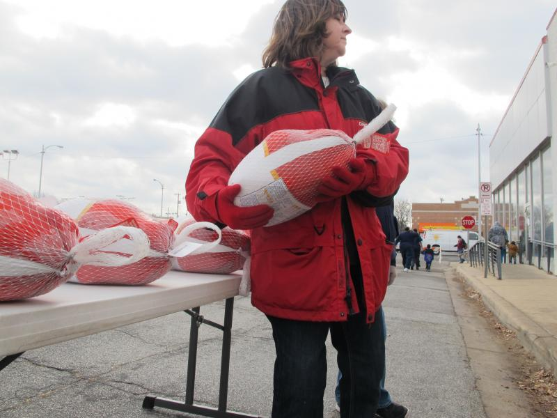 A Cargill employee hands out turkeys to families during the Salvation Army distribution.