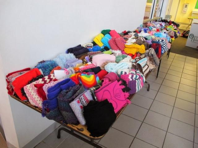 Her table of hats, gloves, and scarves contains many items hand-made by volunteers