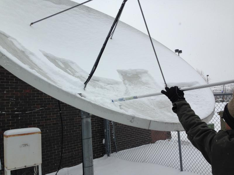 KMUW's engineer braves the weather to scrape the snow out of out the satellite dish so our signal remains clear