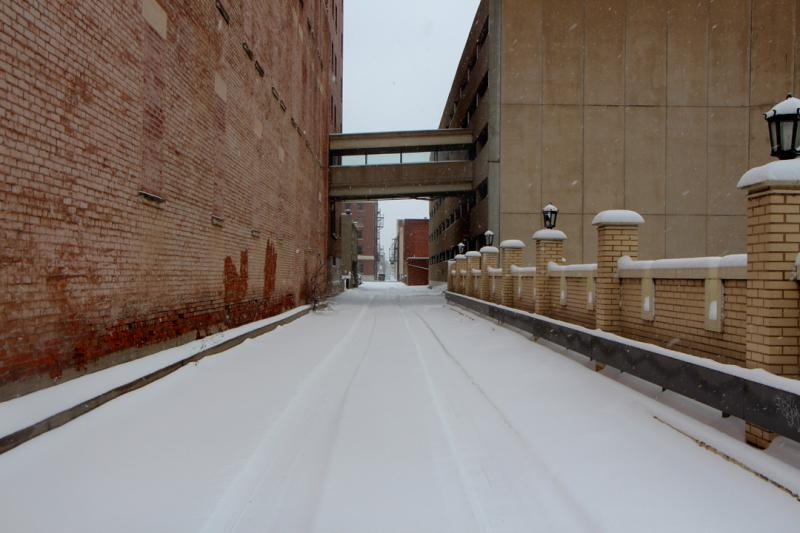 A single pair of tracks lead the way down an alleyway off of Market Street during Tuesday's snow showers.
