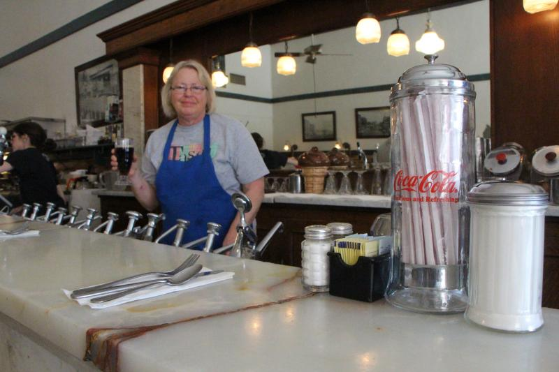 Old Mill Tasty Shop Owner Mary Wright serves a fountain drink.