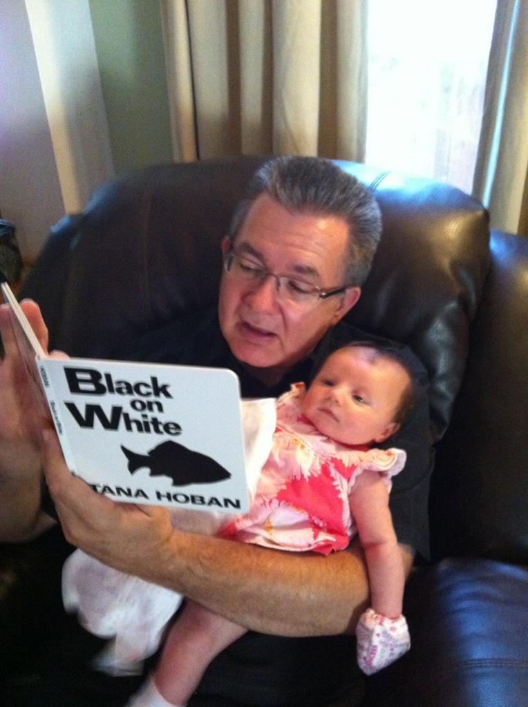Dan reads to his granddaughter, Vayda.