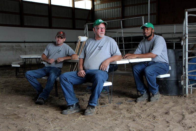 Inmates from Hutchinson Correctional Facility take a break at the prison's wild horse training center.