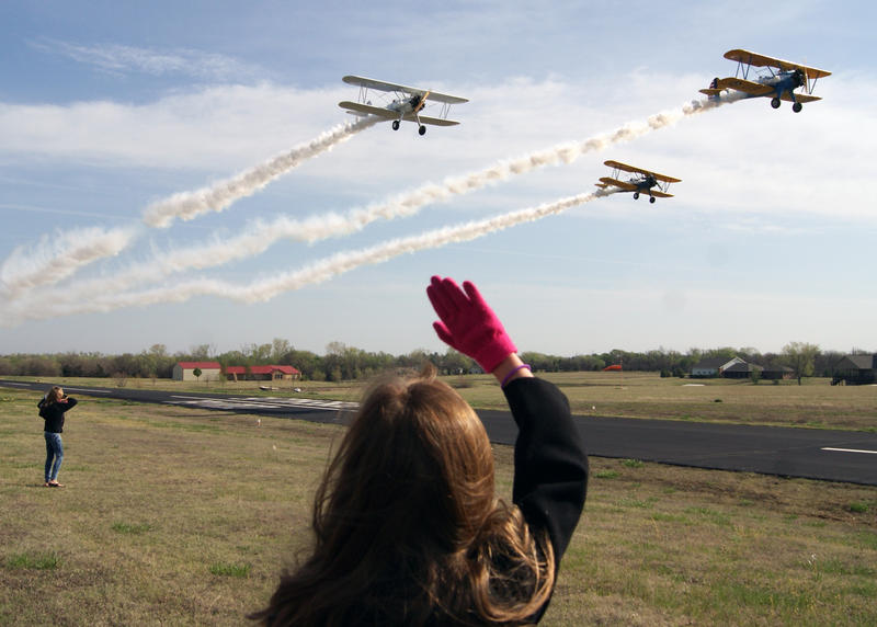 One of the girls from the book club waves as three pilots in Boeing Stearman biplanes fly over the airfield. The planes are from Benton, Kan. and did several passes by the hangar for the girls.