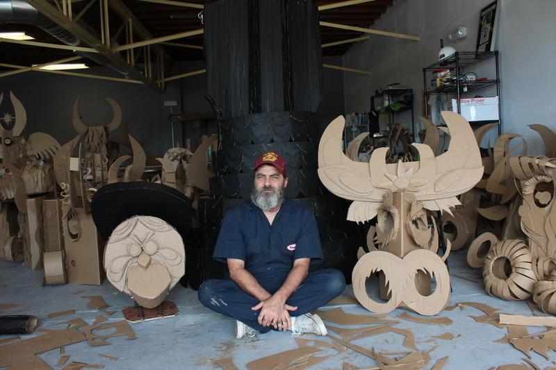Los Angeles-based mulitmedia artist Wayne White sits among his carboard creations