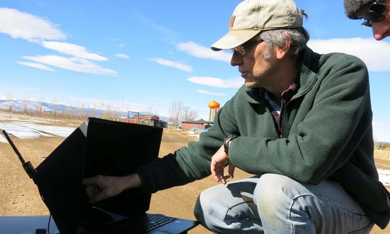 Tom McKinnon with Boulder-based agriculture drone company Agribotix uses in-field technology to program a drone's flight path over a corn field.
