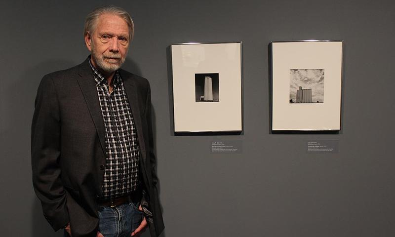 "Larry Schwarm stands in front of photos included in the Wichita Art Museum's new exhibition, ""No Mountains in the Way."""