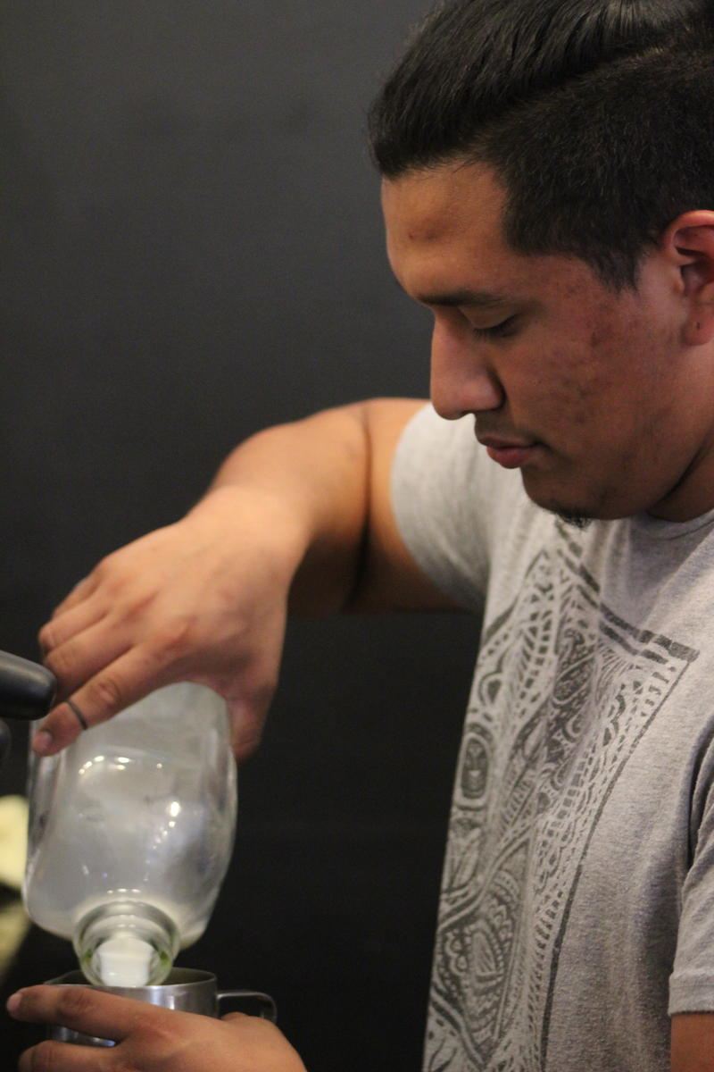 Barista Diego Esquivel pours milk as he competes in a Barista Throwdown. He came in second place.