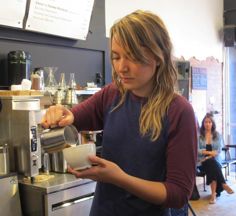 Kristyn Chapman pours milk before making her competition-winning latte art.
