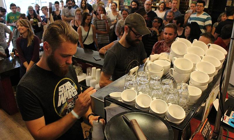 Baristas prepare artful lattes at their stations as onlookers watch on at Reverie Coffee Roasters.