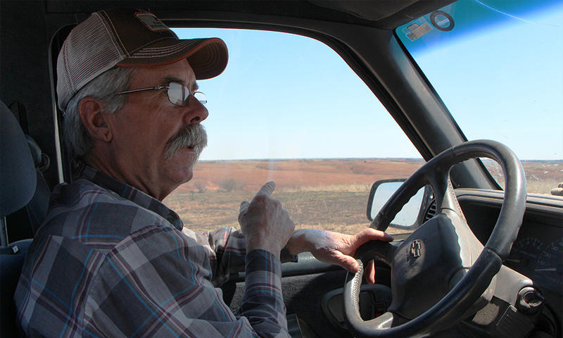 Barber County rancher and volunteer firefighter Dennis Ricke drives through land damaged by a recent wildfire.