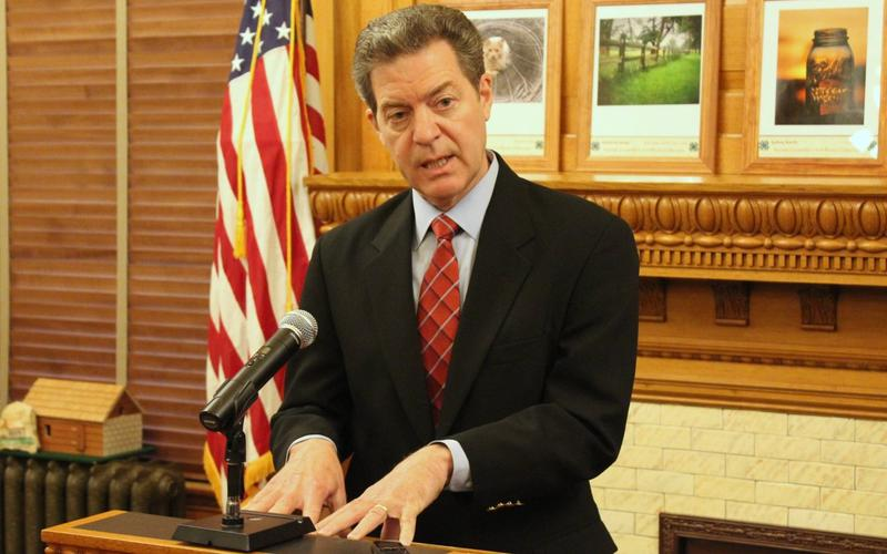 Gov. Sam Brownback speaks to reporters during the bill signing ceremony Monday.