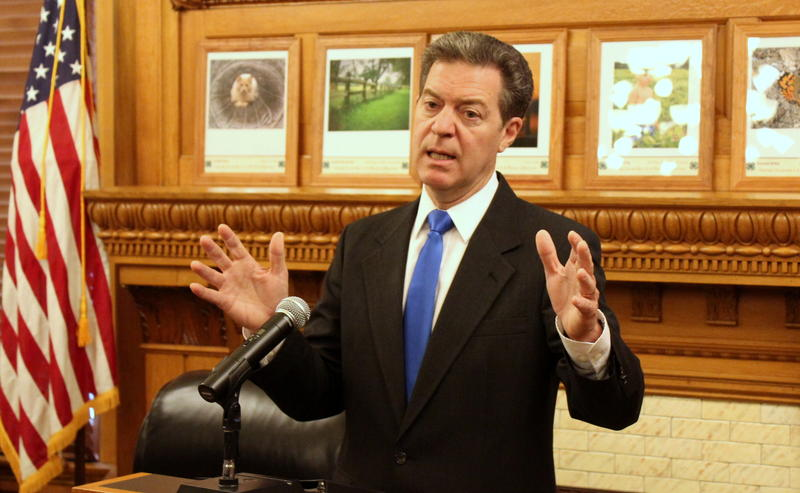 Governor Sam Brownback speaking to reporters.