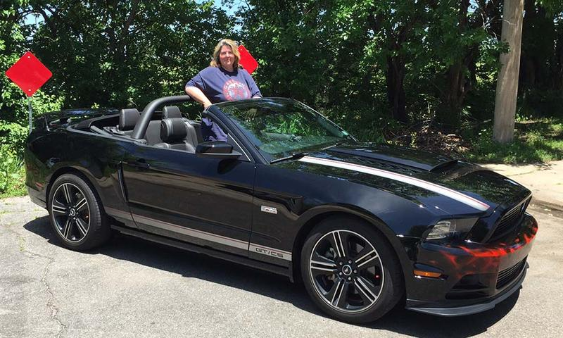 Kelly Keyser stands next to her beloved black-on-black convertible Mustang.