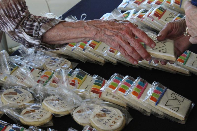 A volunteer hands out Mark Arts cookies at the groundbreaking ceremony Wednesday.