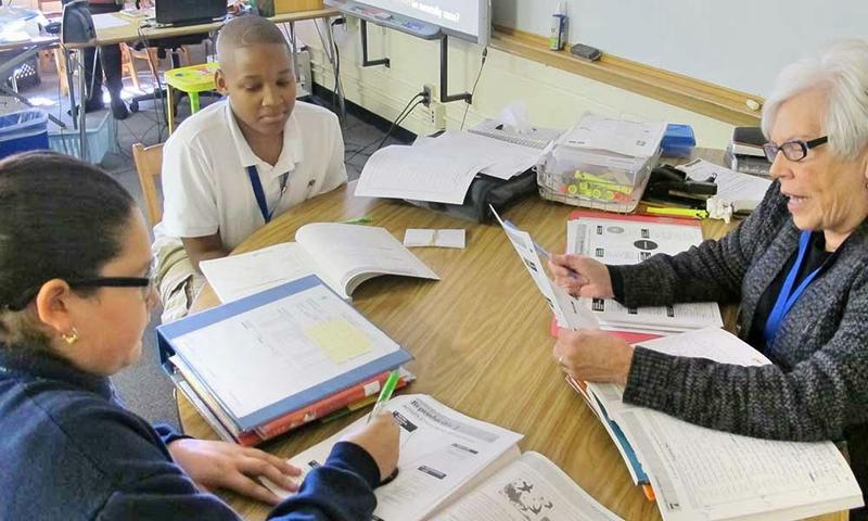 Foster grandparent Judi Fellers helps 8th graders Travone James and Karina Villalobos with their language arts workbooks.
