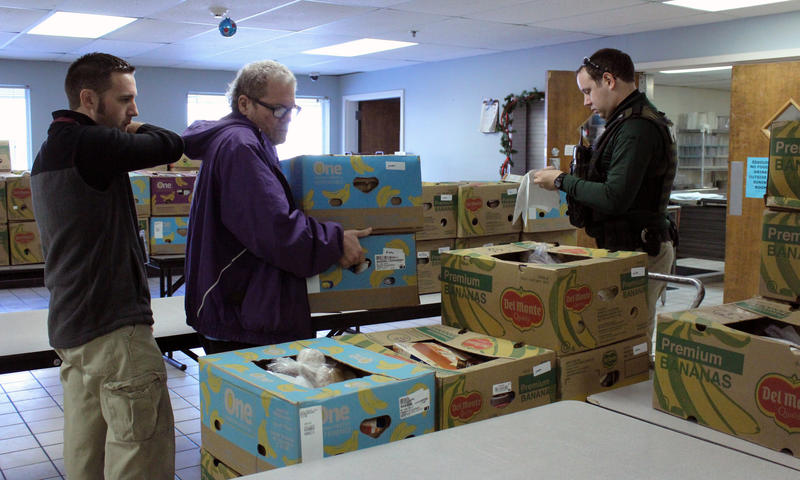 Staff and residents at Wichita's Union Rescue Mission help members of the Wichita Police Department load up boxes of food for families in need.