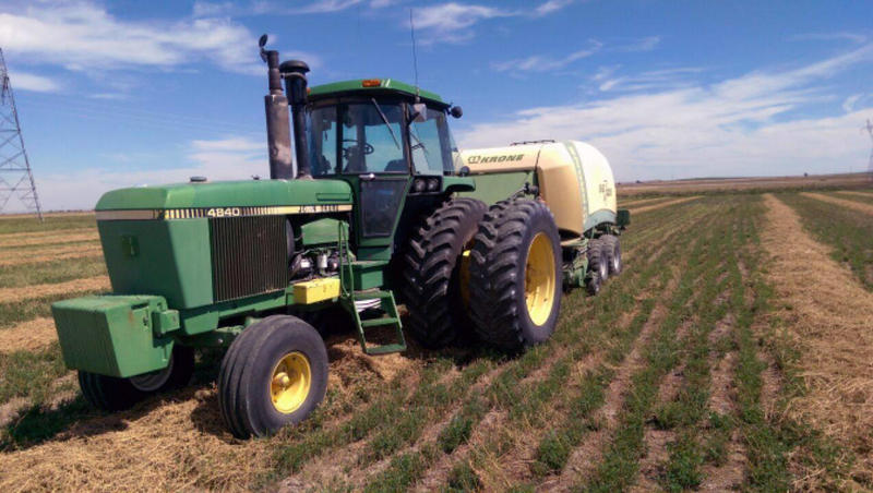 A tractor owned by Nebraska farmer Elliot Chapman stands in a field of alfalfa. Chapman had to sell most of his equipment after experiencing financial trouble.