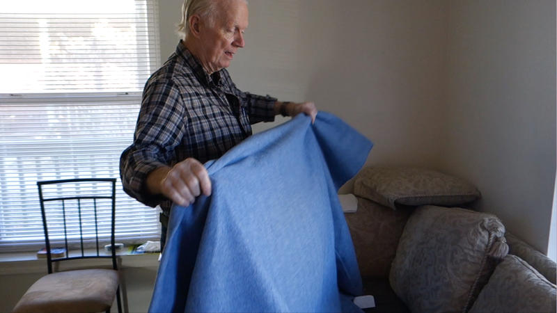 Richard Reser, 71, folds the thin grey blanket he sleeps under each night. Reser is one of more than 1700 non-violent prisoners whose sentences were commuted by Pres. Barack Obama.